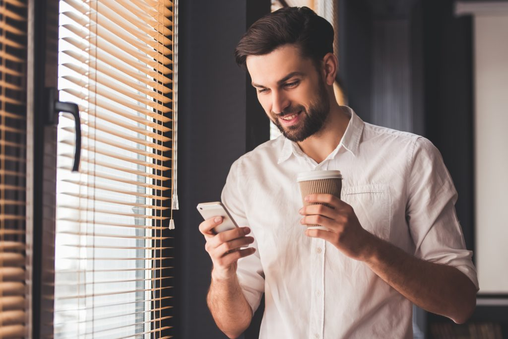 Homem branco usando uma plataforma de gamificação no smartphone enquanto segura um copo da café.